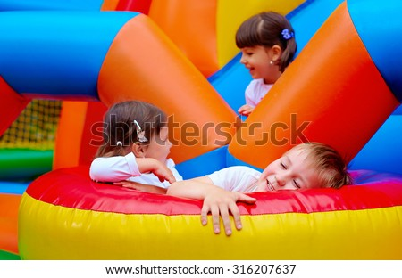 excited kids having fun on inflatable attraction playground - stock photo