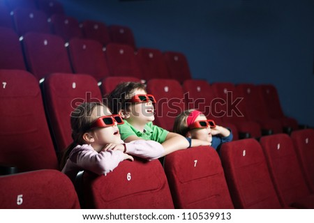 Excited kids watching cartoon in the 3D movie theater - stock photo