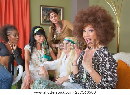 Excited lady in afro sitting with friends in 1960s scene - stock photo