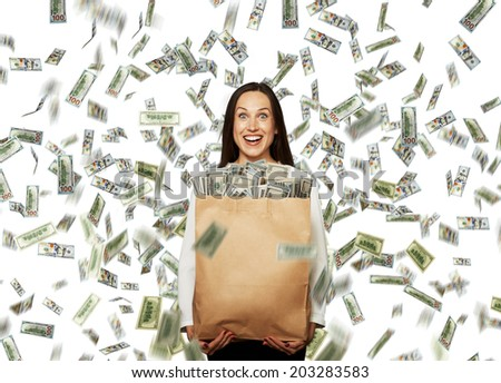 excited laughing businesswoman standing under dollar's rain, holding big paper bag with money and looking at camera - stock photo