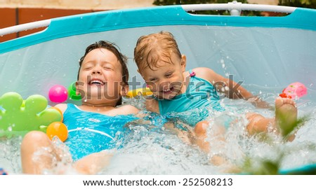 Excited laughing children having fun in kid swimming pool at terrace - stock photo