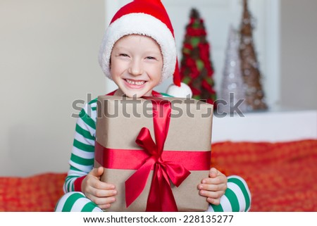 excited little boy in santa hat at christmas time at home holding nicely wrapped present - stock photo