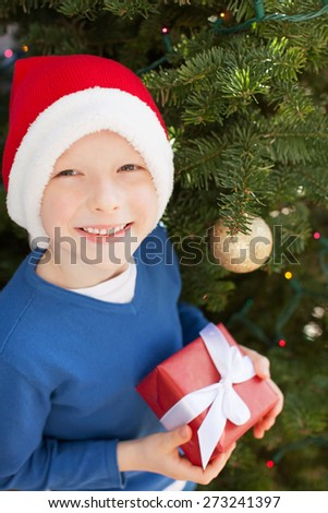 excited little boy in santa's hat holding wrapped present at christmas time - stock photo