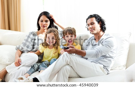 Excited little boy watching TV with his family sitting on a sofa - stock photo