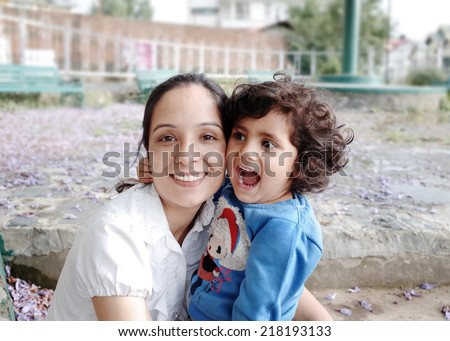 Excited little girl in her mother's arms. - stock photo
