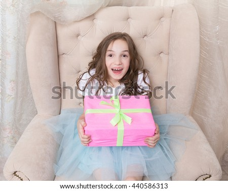 excited little girl just got her present. Cute little girl hold giftbox, sit in chair, smile - stock photo