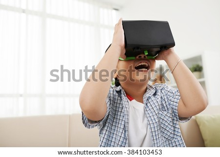 Excited little kid using virtual reality glasses - stock photo