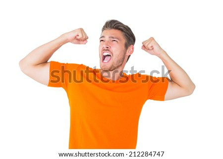 Excited man in orange cheering on white background - stock photo