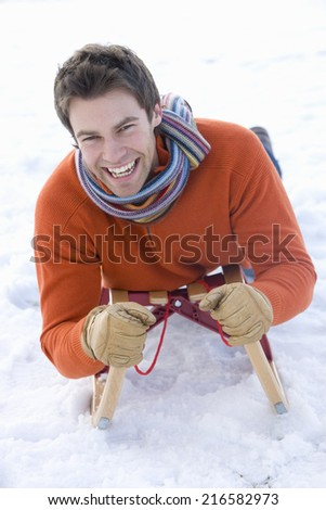 Excited man sledding down snowy field on sled - stock photo