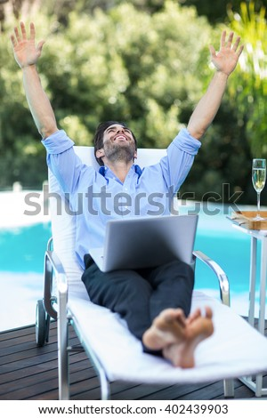 Excited man using a laptop near the pool - stock photo