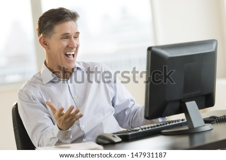 Excited mature businessman shouting while using Desktop PC in office - stock photo
