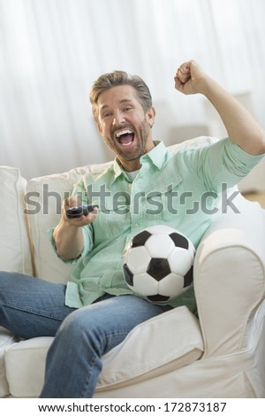 Excited mature man cheering while watching soccer match on sofa at home - stock photo