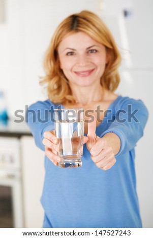 Excited mid adult woman showing thumbs up sign and holding a glass of water - stock photo