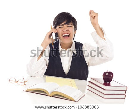 Excited Mixed Race Female Student at Desk with Books on Cell Phone Cheers Isolated on a White Background. - stock photo