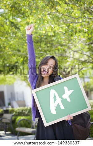 Excited Mixed Race Female Student Holding a Chalkboard With A+ Written on it. - stock photo