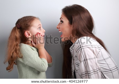 Excited mother and surprising kid girl looking on each other with opened mouth on blue background - stock photo