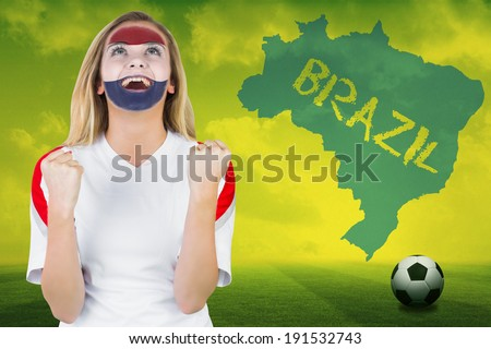 Excited netherlands fan in face paint cheering against football pitch with brazil outline and text - stock photo