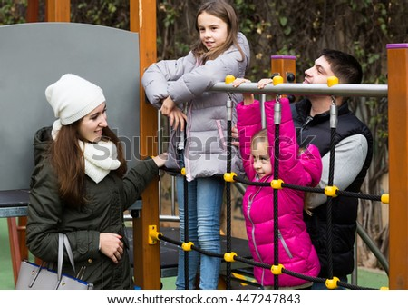 Excited parents with two little positive daughters playing at children's slide