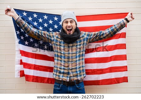 Excited patriot of American style. Excited young man holding American flag while standing against brick wall  - stock photo