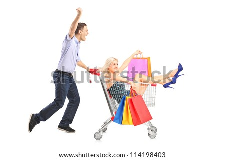 Excited person pushing a shopping cart, happy woman with bags in it, isolated on white background - stock photo