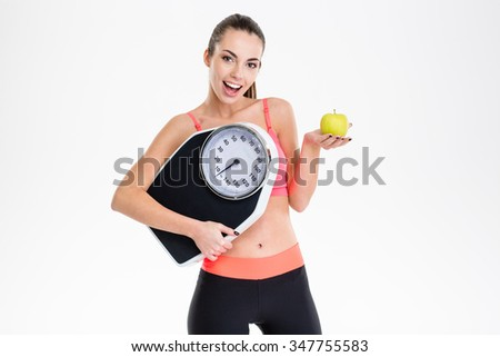 Excited positive fitness girl in tracksuit holding weighing scale and apple over white background - stock photo