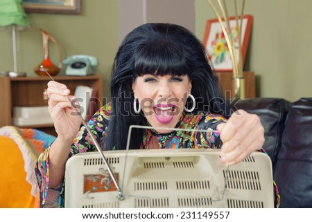 Excited retro 1960s woman adjusting antenna on TV - stock photo