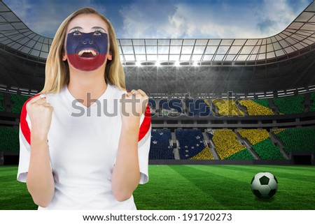 Excited russia fan in face paint cheering against large football stadium with brasilian fans - stock photo
