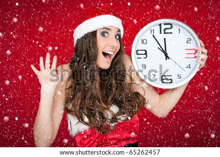 excited santa girl holding clock while snowing - stock photo