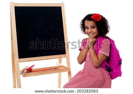 Excited school kid sitting near the blackboard - stock photo