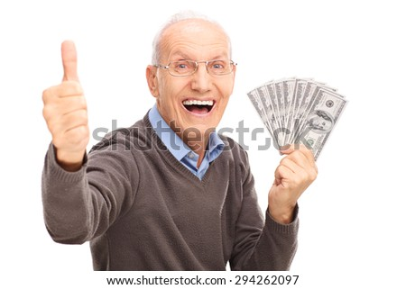 Excited senior gentleman holding a stack of money and giving a thumb up isolated on white background - stock photo