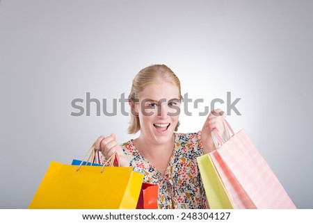 Excited shopaholic holding many paper bags - stock photo