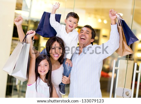 Excited shopping family with arms up holding bags - stock photo