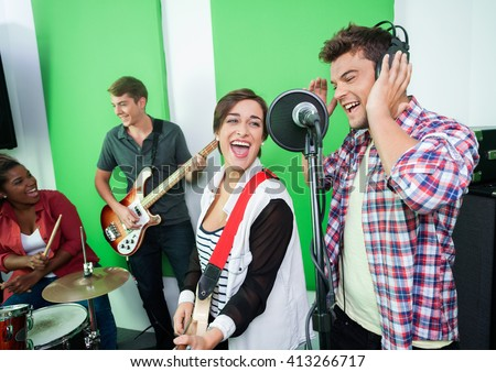 Excited Singers Performing While Colleagues Playing Musical Inst - stock photo