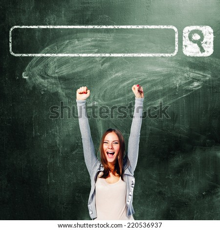excited student woman is standing with chalk board behind her - stock photo