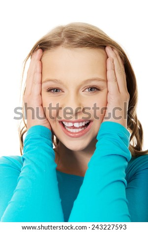 Excited teenage woman holding her head - stock photo