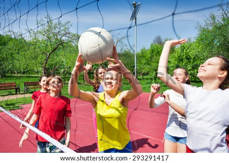 Excited teens play near volleyball net on court - stock photo
