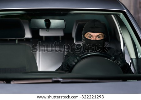 Excited thief getting away with the stolen car. - stock photo
