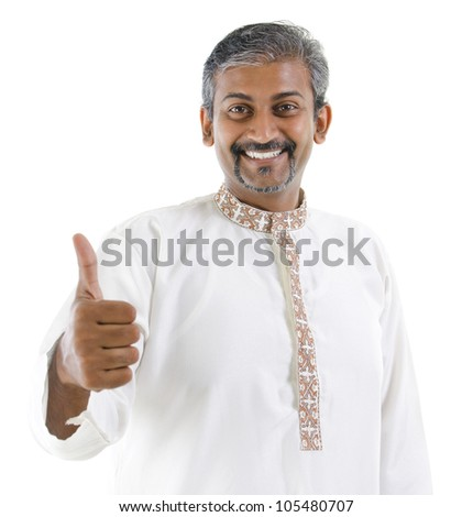 Excited thumb up Indian man in traditional costume kurta dhoti isolated on white background - stock photo
