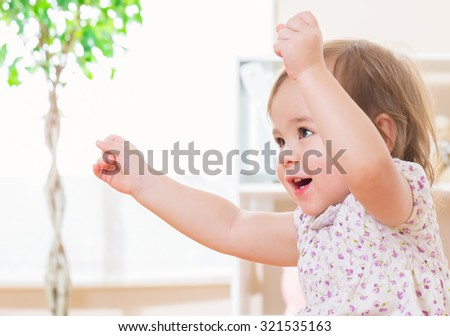 Excited toddler girl with a great big smile - stock photo