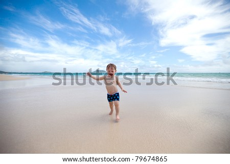 Excited toddler running away from the waves towards the camera on a tropical beach - stock photo