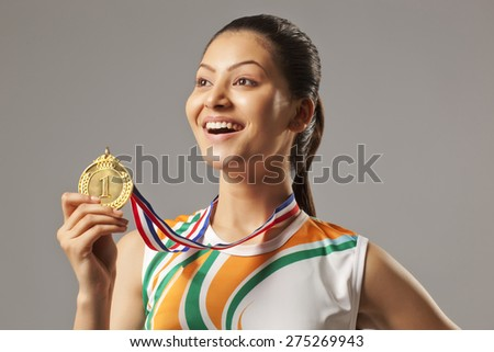 Excited woman holding gold medal isolated over gray background - stock photo