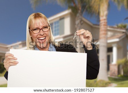 Excited Woman Holding House Keys and Blank Real Estate Sign in Front of Nice New Home. - stock photo
