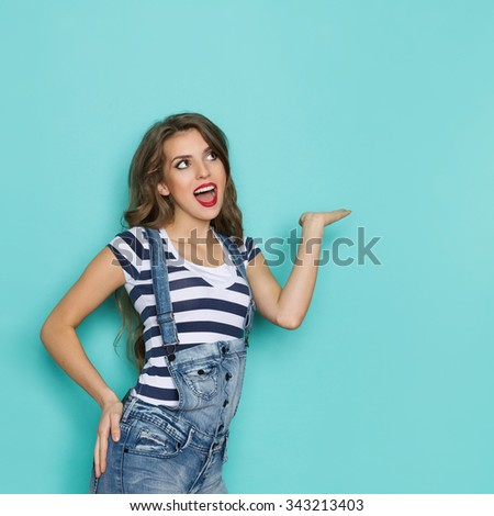 Excited woman in dungarees and blue striped shirt presenting product and looking at copy space. Three quarter length studio shot on teal background. - stock photo
