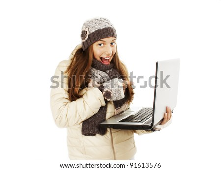 Excited woman pointing at netbook laptop screen. Winter style. Isolated on white background - stock photo