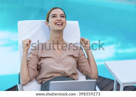 Excited woman relaxing on sun lounger with laptop near the pool - stock photo