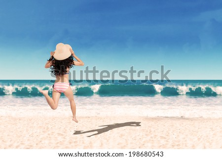 Excited woman running at beach into the sea. Shoot at summertime - stock photo