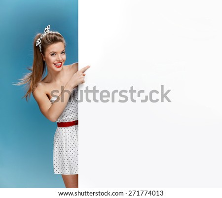 Excited woman showing empty blank banner with copy space for text / photo set of young American pin-up model on blue background with space for text - stock photo
