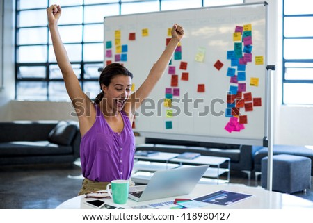 Excited woman sitting on table with digital tablet and laptop in office - stock photo