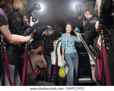 Excited woman with cleaning equipment getting out of limousine in front of paparazzi - stock photo