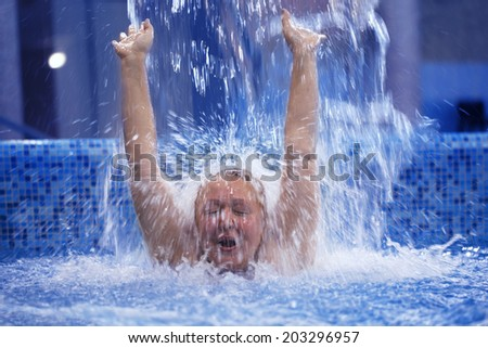Excited woman with her hands up enjoying strong shower in the swimming pool - stock photo